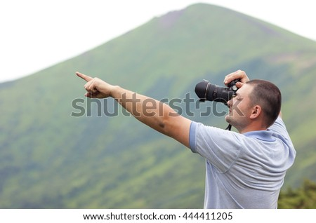 Photographer with a camera  taking picture of mountains pointing with finger - stock photo