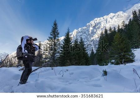 Photographer with backpack shooting a landscape with snowy mountains