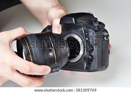 Photographer with big lens and digital SLR camera close-up - stock photo