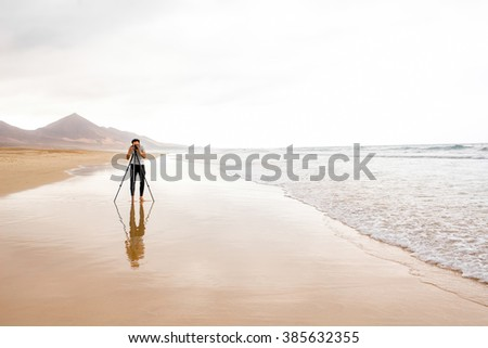 Photographer with camera and tripod photographing beautiful sandy beach. General plan with copy space - stock photo
