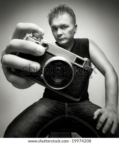 photographer with camera portrait shoot wide angle lens on gray background - stock photo