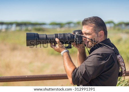 Photographer with dslr taking pictures outdoor in summer.