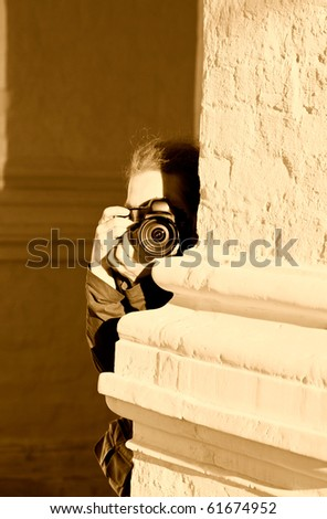 photographer with eguipment on the  wall's bakground - stock photo
