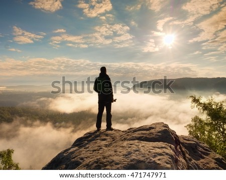 Photographer with folded tripod on end of cliff thinking. Heavy fogy landscape, misty sunrise in  beautiful valley below