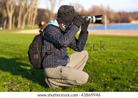 Photographer with tele lens making photo. Outdoor - stock photo