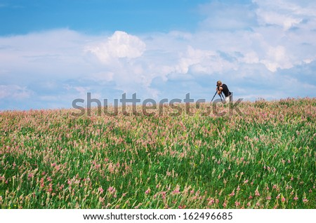 Photographer work in spring meadow. - stock photo