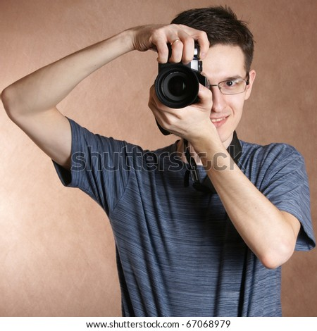 photographer, young man with professional camera - stock photo