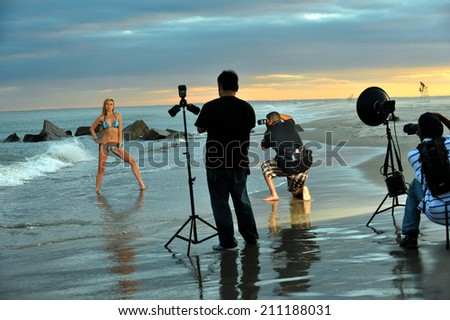 Photographers and bikini model in summer photoshooting on the beach during sunset time. - stock photo