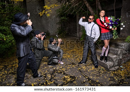 Photographers are taking a picture of lovely couple against grunge wall  - stock photo