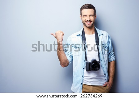 Photographers choosing it. Handsome young man with digital camera pointing away and smiling while standing against grey background - stock photo