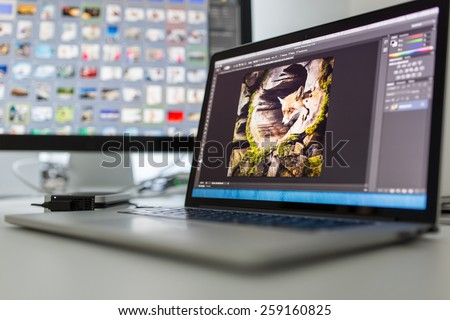 Photographers computer with photo edit apps/programs running  - stock photo