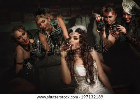 Photographers is taking a picture of a beautiful cabaret girls - stock photo