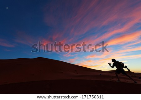 Photographers playing on dunes of desert Sahara at sunset, Morocco