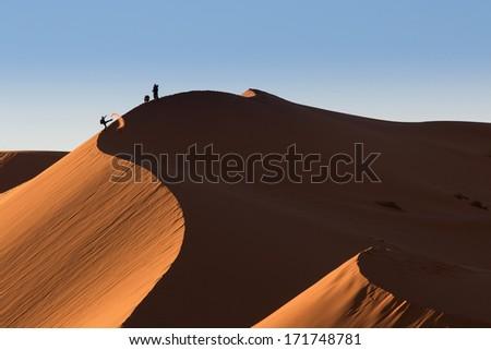 Photographers playing on dunes of desert Sahara, Morocco - stock photo