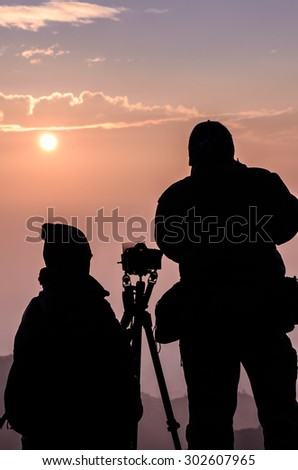 Photographers silhouette in outdoor with dramatic sunrise.