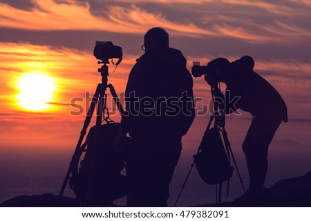 Photographers Silhouettes On Cliff Against Colorful Twilight Sky