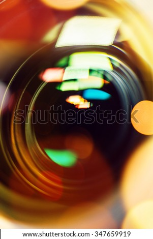 Photographic camera lens close up front view with bokeh light - stock photo