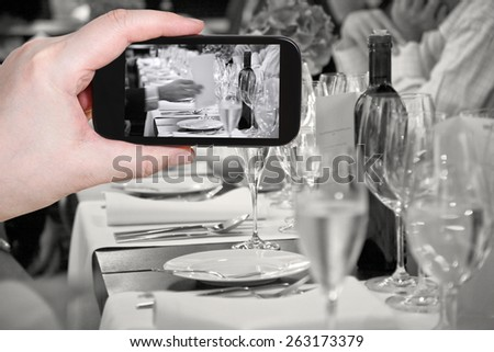 photographing food concept - tourist takes picture of beginning of official dinner in restaurant on smartphone, - stock photo