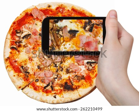 photographing food concept - tourist takes picture of italian pizza with mushrooms and prosciutto cotto on smartphone, Italy - stock photo