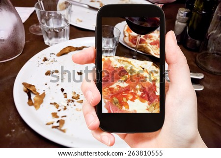 photographing food concept - tourist takes picture of italian pizza with parma ham and glass of red wine on smartphone, Italy - stock photo