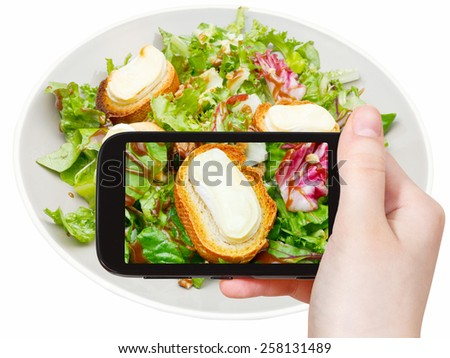 photographing food concept - tourist taking photo of green salad with goat cheese on mobile gadget, Italy