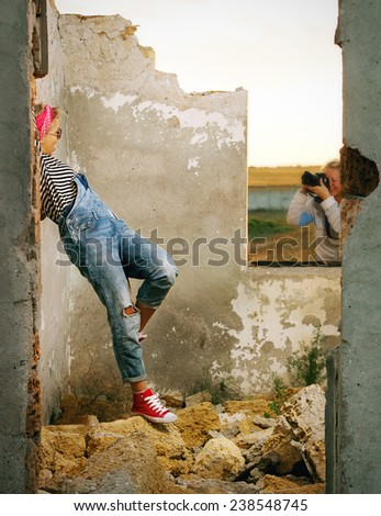 photographing girls on a construction site in denim overalls and sneakers