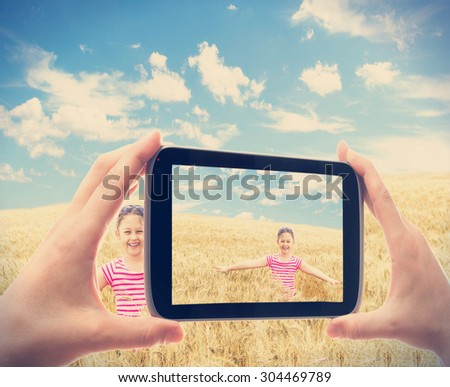 photographing smartphone child in wheat - stock photo