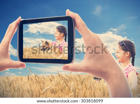 photographing smartphone girl with a dog in a wheat field - stock photo