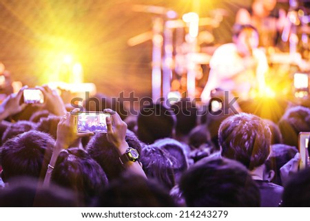 photographing with smartphone during a concert - stock photo