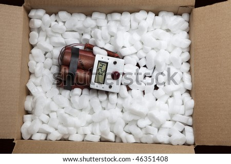 Photographs of red sticks of dynamite with a timer in a cardboard box - stock photo
