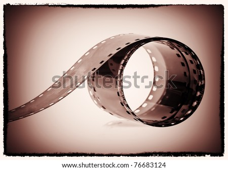 Photography film reel on a sepia vignetted background - stock photo