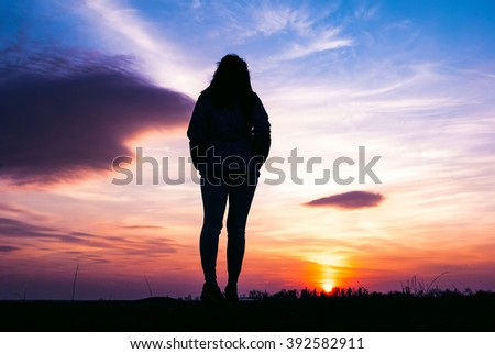 Photography of girl stand at the sunset and looking away. Silhouette on the landscape background - stock photo