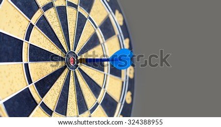 Photography of vintage yellow and black colors darts. Success hitting target aim goal achievement. Blue Dart in bull's eye. copy space. soft focus - stock photo