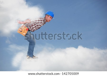 Photomontage of a young workman walking on the clouds - stock photo