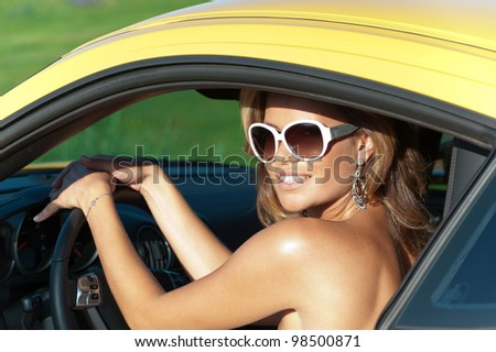 Photos happy young blonde in an elegant yellow Porsche - stock photo