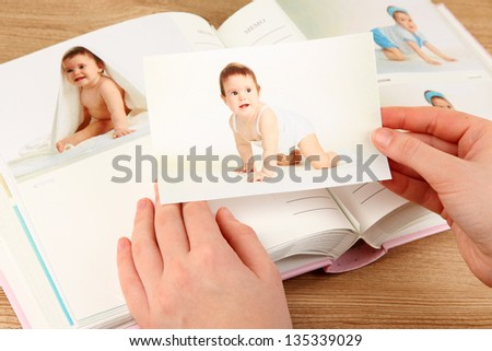 Photos in hands and photo album on wooden table - stock photo