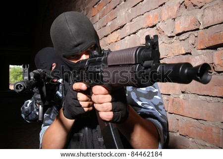 Photos of heavy equiped soldiers or terrorists in black masks with automatic guns. - stock photo