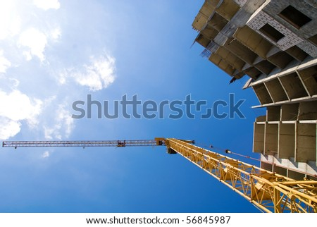 Photos of high-rise construction cranes and unfinished house against the blue sky with clouds. Taken from the bottom up - stock photo
