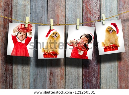 Photos of little girl and dog wearing Santa Claus hat  hanging in the old room. - stock photo
