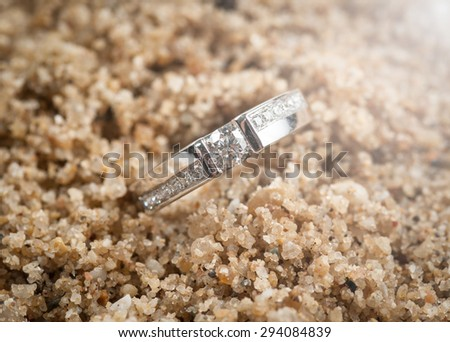 Photos of wedding rings on sand at beach - stock photo