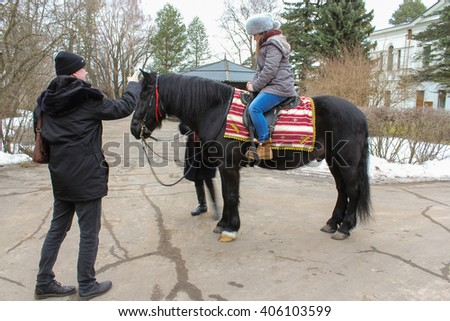Photos on a horse. Vitoslavlitsy, Russia - March 12, 2016. Domestic horses live and work in urban areas.