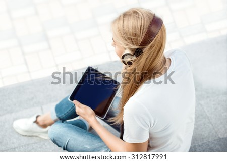 Photoset of a happy young woman on the road with zebra crossing, drinking coffee from a takeaway coffee cup, wearing music headphones and buying music on tablet online against road background - stock photo