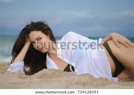 Photoshoot model. Young beautiful girl on the beach in a white shirt with long flowing hair sitting on the sand by the sea.