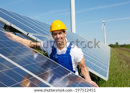 Photovoltaic engineer or installer installing solar panels  - stock photo