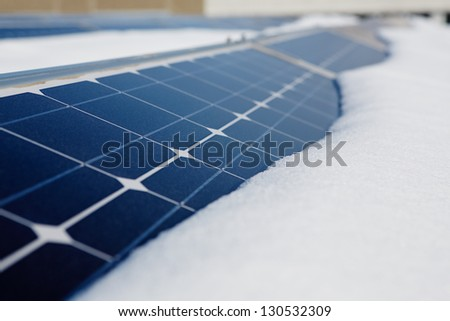 photovoltaic modules in winter covered by snow - stock photo