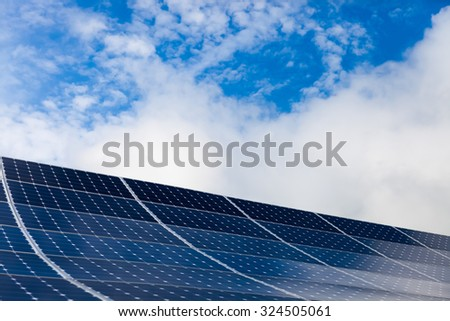 Photovoltaic modules of solar panels with sky on background - stock photo