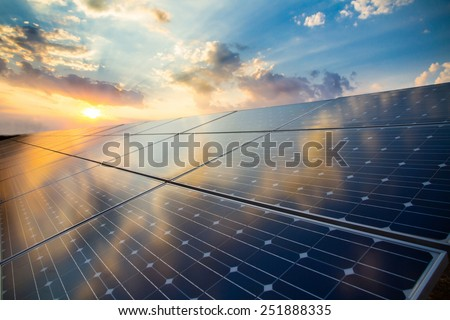 Photovoltaic modules on the background of sunset and cloudy sky - stock photo