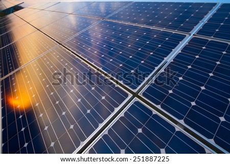 Photovoltaic modules reflect sunset light and cloudy sky - stock photo