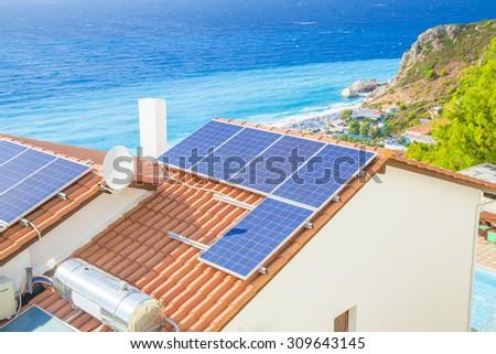 photovoltaic panels - house sea - stock photo