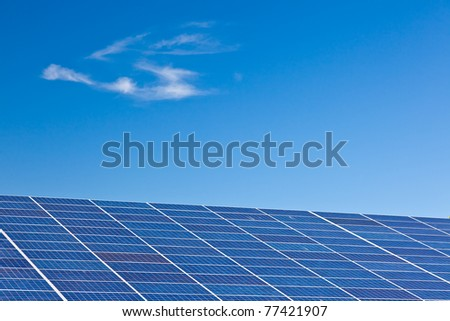 Photovoltaic panels in a solar power plant over a deep blue sky. - stock photo